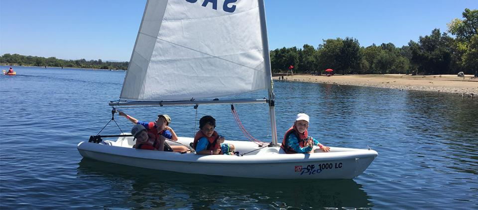 kids in a sailboat smiling at the camera