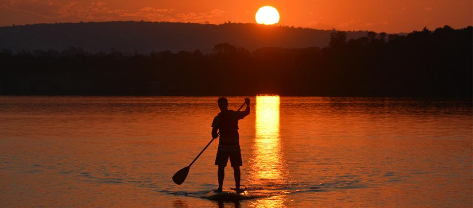 sunset stand up paddler