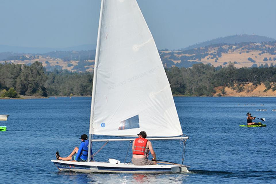 sailboat and kayakers on the water