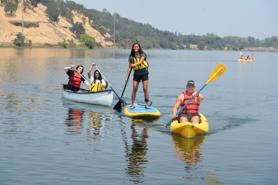 two girls in a canoe, on girl on a stand up paddle board and one man in a kayak