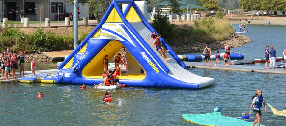 kids and adults playing on an inflatable structure in the water