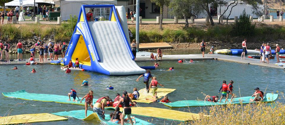 people playing on an inflatable structure on the water
